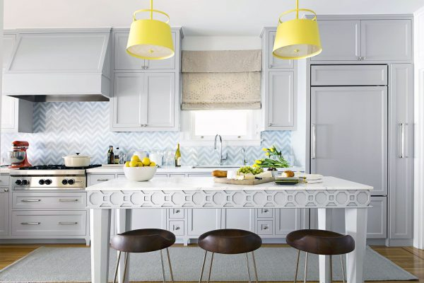 a stunning modern white kitchen with yellow lamps