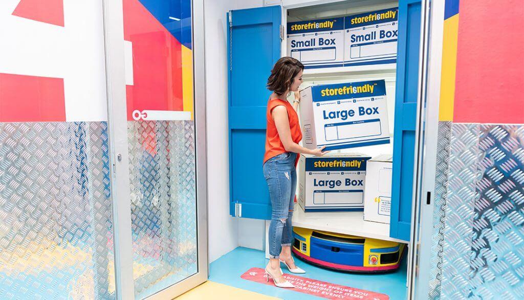 A woman placing a storefriendly box inside a storage unit