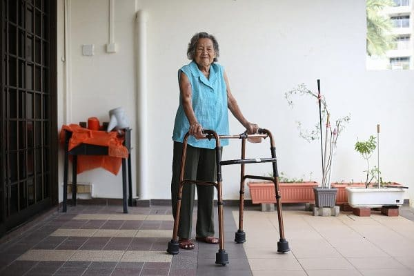 an elderly woman walking with a walking aid