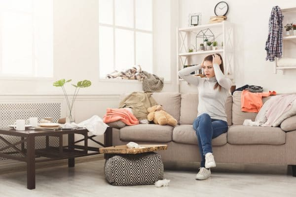 a woman stressed over her clutter while sitting on her sofa