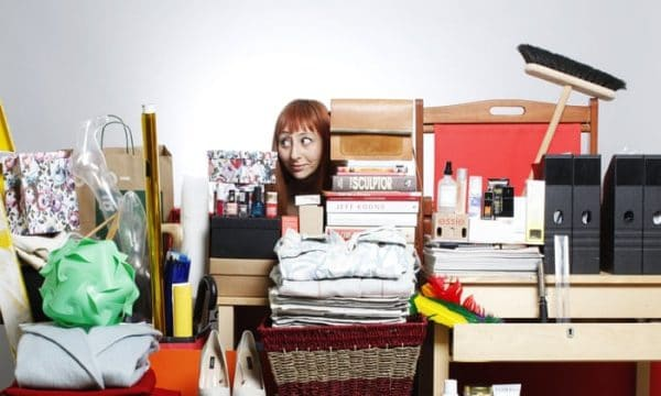 a woman looking at all her clutter on the table