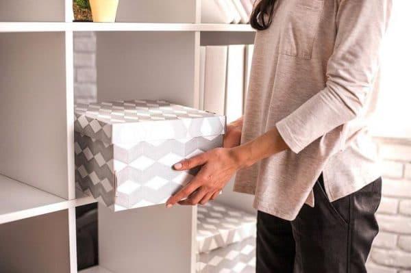 a woman placing a grey cardboard box on the shelf