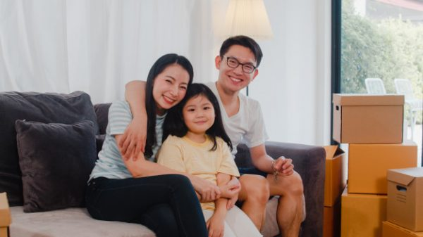 a happy young asian family sitting on a couch with cardboard boxes beside them