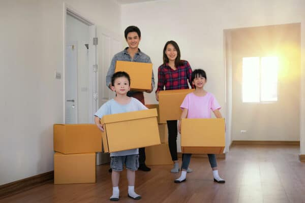 happy asian family with cardboard boxes in their new house