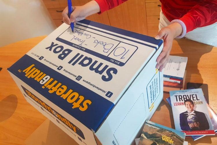A woman writing the address on a storefriendly box