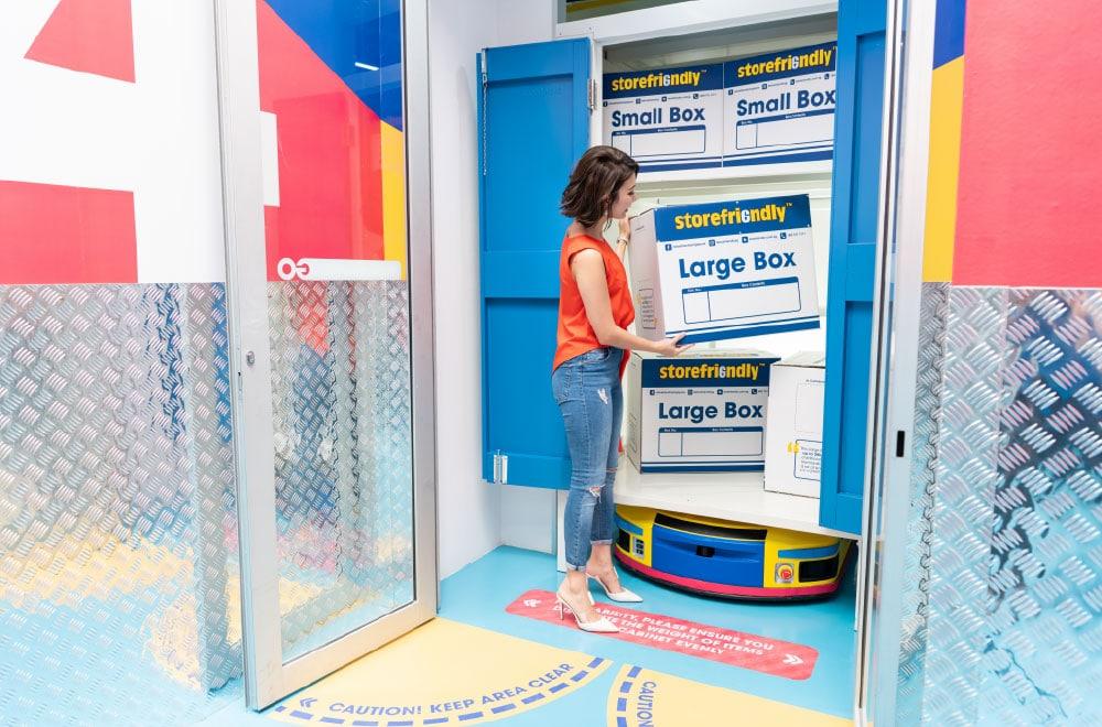 A woman storing a cardboard box inside a storage unit