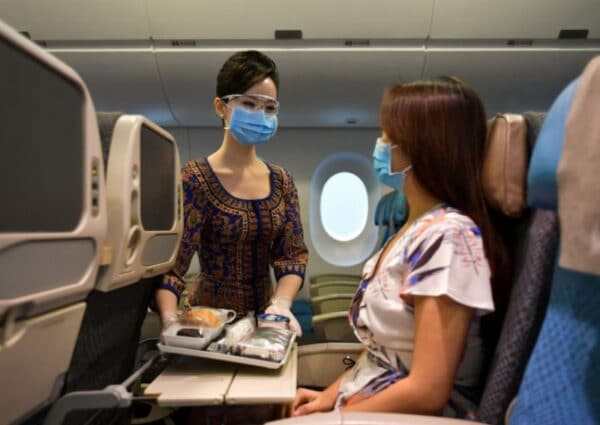 A flight attendant tending to a passenger on the plane