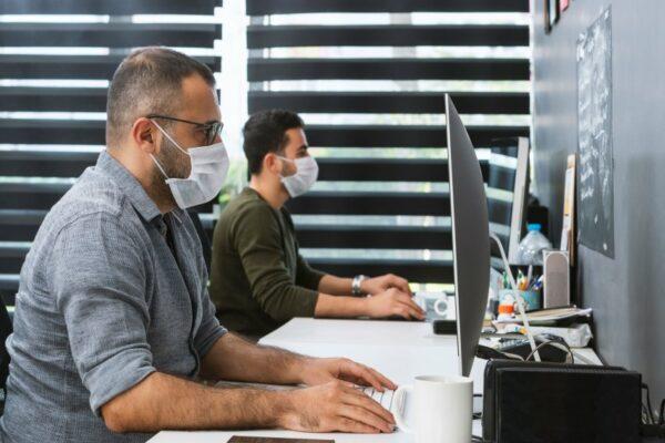 two men wearing face masks working on their desks