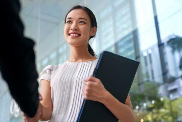 an asian businesswoman shaking her hand