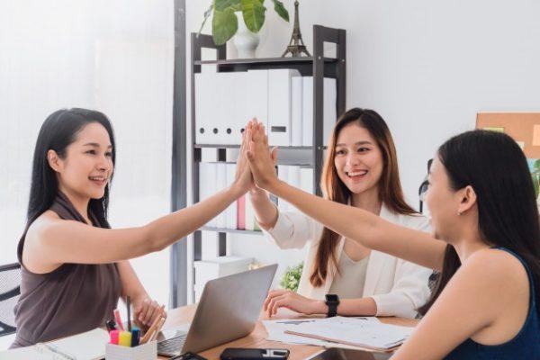a group of beautiful asian women doing a high five
