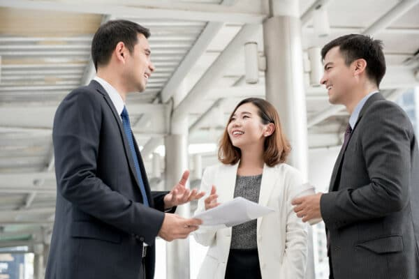 a group of 3 people in the office talking