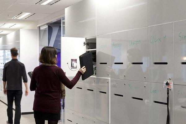 A woman putting a book inside a storage locker