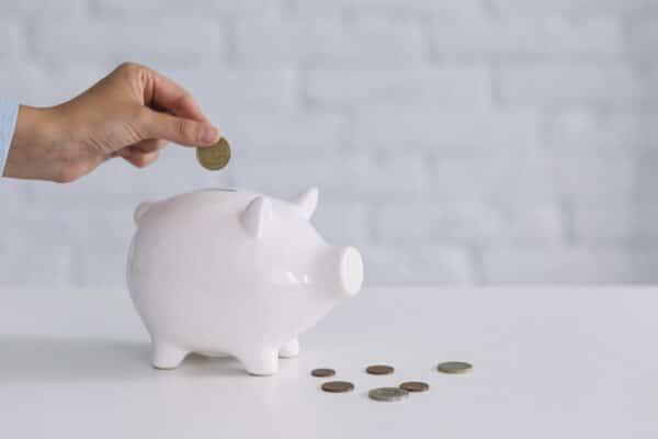 A hand putting a coin inside a porcelain piggy bank