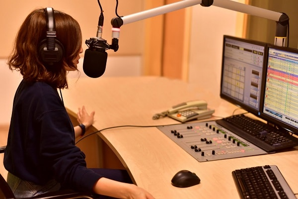 A woman talking on the microphone inside a studio